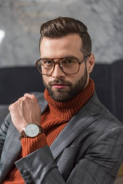 portrait of handsome man in formal wear and glasses looking at camera