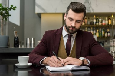 serious handsome businessman in formal wear sitting and writing in notebook at table in restaurant