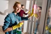 krásná dívka v gumové rukavice hospodářství, zařízení pro čištění a při pohledu na fotoaparát v bytě