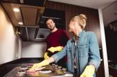 usmívající se pár v gumové rukavice čištění kuchyní a nábytku společně a při pohledu na sebe