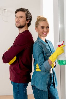 handsome man and smiling girl in rubber gloves standing back to back and looking at camera in apartment