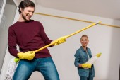 Fotografie happy man smiling and performing with mop and cheerful girl holding duster at background