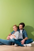 Photo pregnant girl touching belly and sitting on floor with smiling husband by green wall