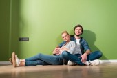 smiling man and pregnant wife sitting on floor and looking at camera