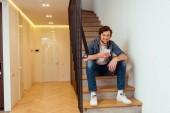 usmívající se muž sedí na schodech a pomocí smartphonu