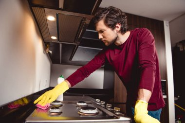 serious man in rubber gloves cleaning kitchen