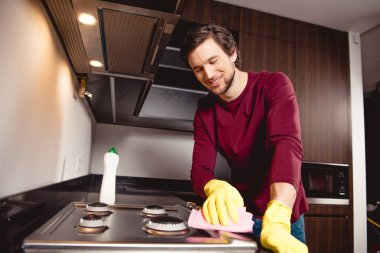 handsome man in rubber gloves cleaning kitchen and smiling