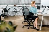 boční pohled na krásná obchodnice sedí na pracovišti s notebookem a notebook v úřadu s kole