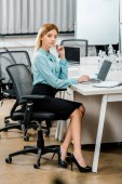 side view of beautiful businesswoman sitting at workplace with laptop and notebook