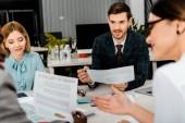 vista parziale di businesspeople multietniche che ha discussione durante la riunione in ufficio