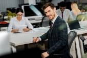 Selektivní fokus mladý podnikatel v obleku a mnohonárodnostní kolegy v kanceláři