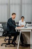 mladý podnikatel sedí na pracovišti s podnikatelka v úřadu