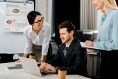 usmívající se spolupracovníky mají schůzku v kanceláři