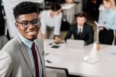 Fotografie Selektivní fokus úsměvu, americký podnikatel a jeho kolegové za pracovišti v úřadu