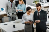 Photo high angle view of multiracial businesspeople with coffee to go and smartphone in office