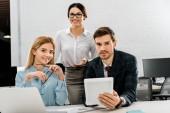 portrét podnikatele s tabletem a podnikatelky na pracovišti s přenosným počítačem v kanceláři