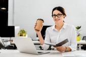 mladá podnikatelka v brýlích s kávou jít a poznámkového bloku na pracovišti s přenosným počítačem v kanceláři