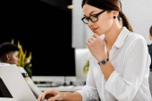 Photo young businesswoman in eyeglasses working on laptop at workplace in office