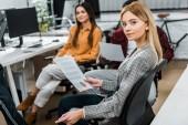 szelektív összpontosít, a fiatal üzletasszony közelében többnemzetiségű kollégák a munkahelyen, az irodai papírok