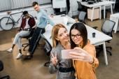 mosolyogva üzletasszonyok vesz selfie smartphone-ban Hivatal mögött többnemzetiségű munkatársaival