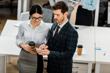 high angle view of businesspeople using smartphone in office