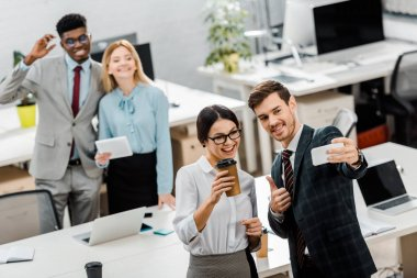 high angle view of multiracial businesspeople taking selfie on smartphone in office