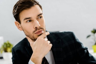 portrait of thoughtful businessman in suit looking away in office
