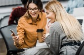 Fotografie Fröhliche Geschäftsfrauen nutzen Smartphone am Arbeitsplatz im Büro