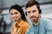 Fotografie smiling call center operators in headsets looking at camera in office