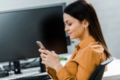 side view of young businesswoman using smartphone in office