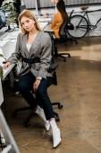 Fotografia giovane imprenditrice guardando la telecamera in ufficio