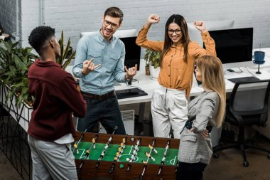 happy multicultural business colleagues playing table football together in office
