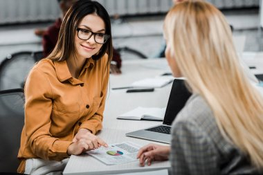 young businesswomen with papers at workplace in office