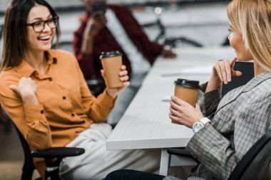 smiling young businesswomen with coffee to go at workplace in office