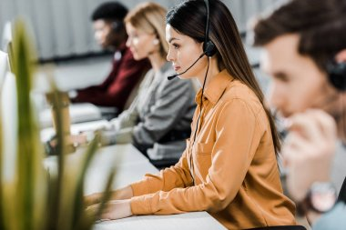 Selective focus of multiethnic call center operators working in office stock vector