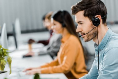 selective focus of call center operator in headset working in office