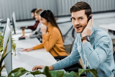 selective focus of call center operator looking at camera while multiethnic colleagues working in office