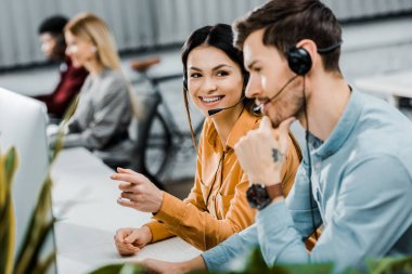selective focus of smiling call center operators and multiethnic colleagues behind in office