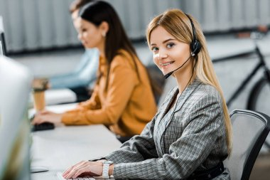Selective focus of smiling call center operator looking at camera in office stock vector
