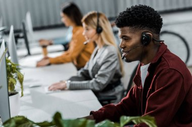 multicultural call center operators with headsets at workpalce in office