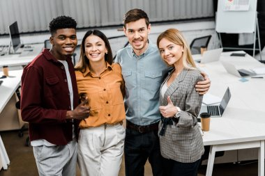 portrait of young happy multiracial business colleagues showing thumbs up in office