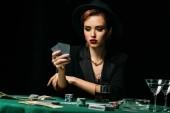 atraktivní dívka v bundě a klobouk hrát poker a při pohledu na karty v kasinu