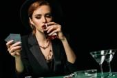 atraktivní dívka v bundě a klobouk pít whiskey a při pohledu na poker karty v kasinu