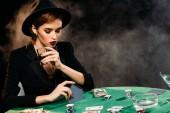 Fotografia ragazza pensierosa attraente in giacca e cappello di giocare a poker e che tiene il bicchiere di whisky in casinò