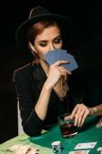 atraktivní dívka v bundě a čepici pokrývající obličej s poker karet v kasinu