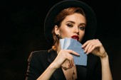 beautiful girl in jacket and hat covering face with poker cards and looking at camera isolated on black