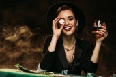 Fotografie happy attractive girl in jacket and hat holding glass of whiskey at poker table and covering eye with casino chip