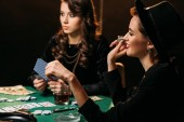 Fotografie attractive smiling girls playing poker at table in casino