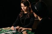 krásné ženy v černých šatech, hrát poker v kasinu u stolu