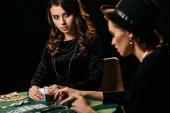 Fotografie atraktivní dívky hrát poker u stolu v temné místnosti v kasinu